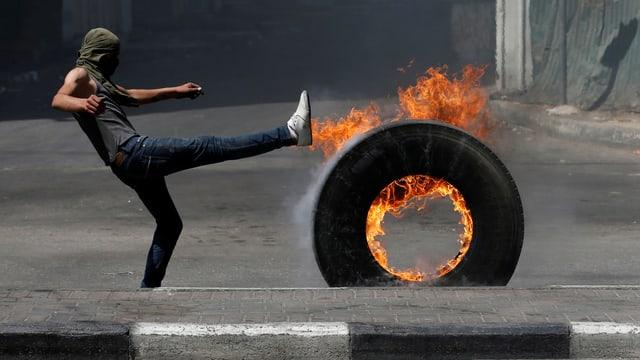 Mann mit brennendem Reifen