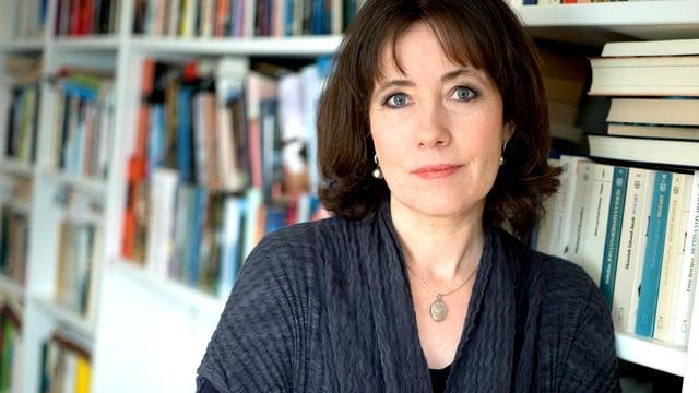 Frau mit dunklen Haaren vor einem Bücherregal.