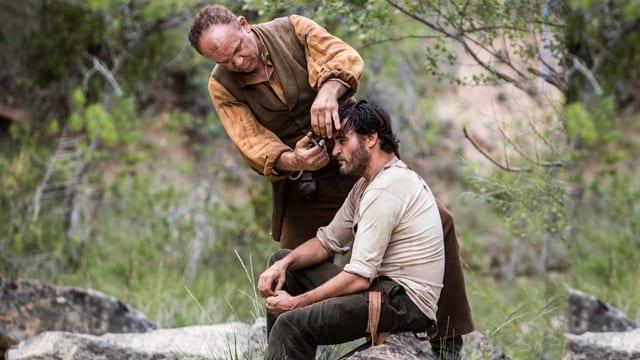Ein Cowboy schneidet einem anderen in der Natur die Haare.