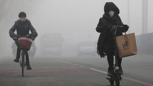 Velofahrer in Peking mit einer Schutzmaske.