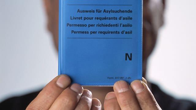 Ein Mann hält einen blauen Ausweis vor sein Gesicht.