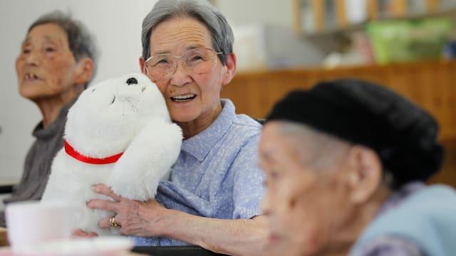 Eine alte japanische Frau hält eine weisse Roboter-Robbe und lächelt.