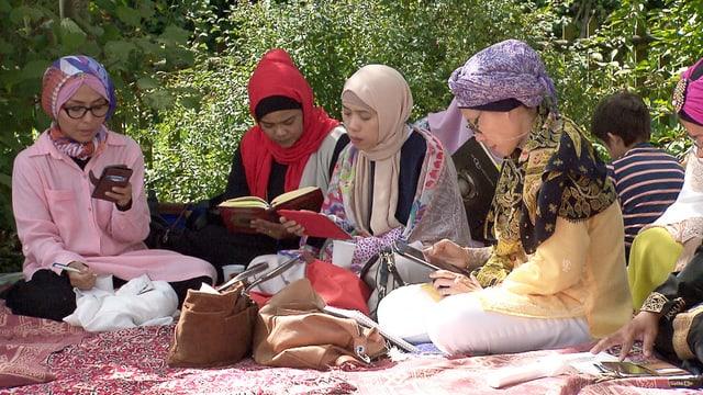 Muslimische Frauen sitzen in einem Garten auf bunten Tüchern