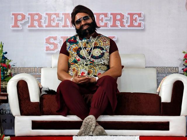 Gurmeet Ram Rahim Singh auf einem Sofa sitzend.