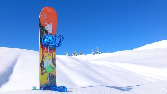 in snowboard en la naiv cun in tschiel blau.