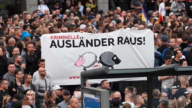 Demonstranten mit Transparent mit SVP-Schafen (schwarz und weiss)