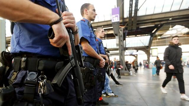 Schwer bewaffente Polizisten stehen in der Bahhhofhalle.
