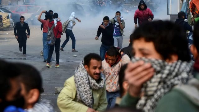Jugendliche bei einer Demo: Die einen werfen Steine, die andern halten schützend Schals vors Gesicht.