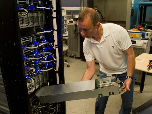 Mann schiebt einen Server ein ein Rack.