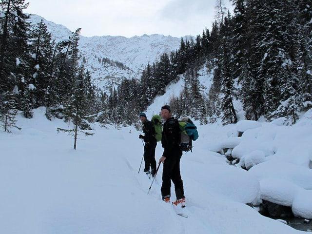 Zwei Männer mit Ski und Rucksack im verschneiten Wald