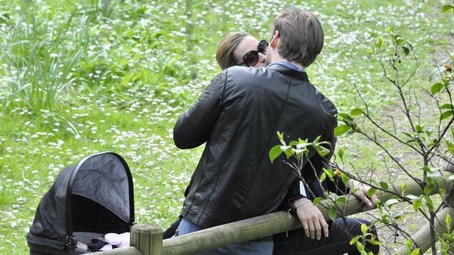Michelle Hunziker und Tomaso Trussardi küssen sich. Daneben steht ein schwarzer Kinderwagen.