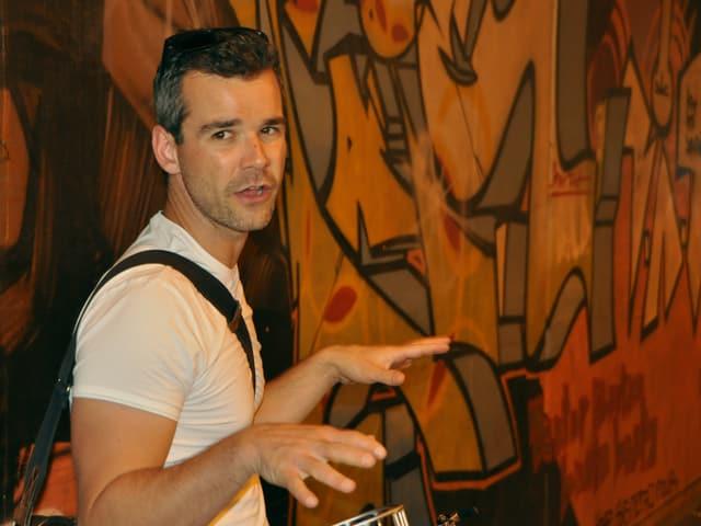David Lucco steht vor einem Graffiti.