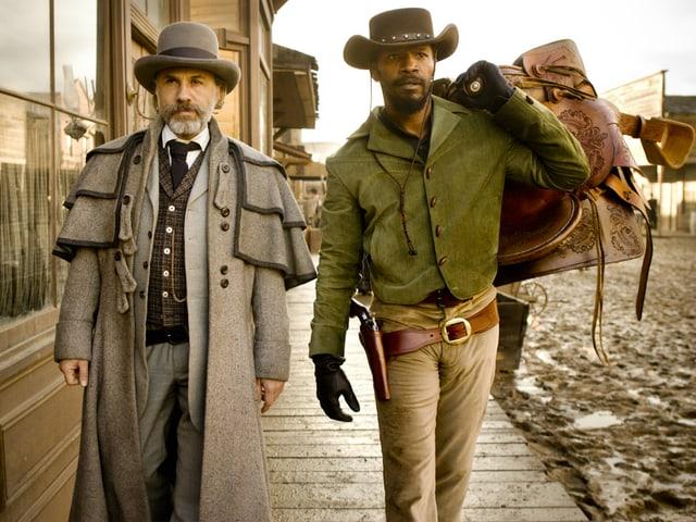 Kopfgeldjäger Dr. King Schultz und der Sklave Django (Jamie Foxx) laufen durch eine Strasse im Wilden Westen.