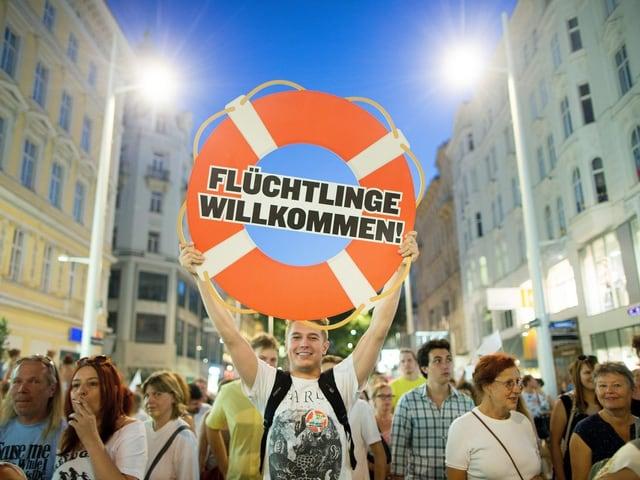 Demonstration in Wien. Demonstrant hält Schild hoch mit der Aufschrift: Flüchtlinge willkommen.