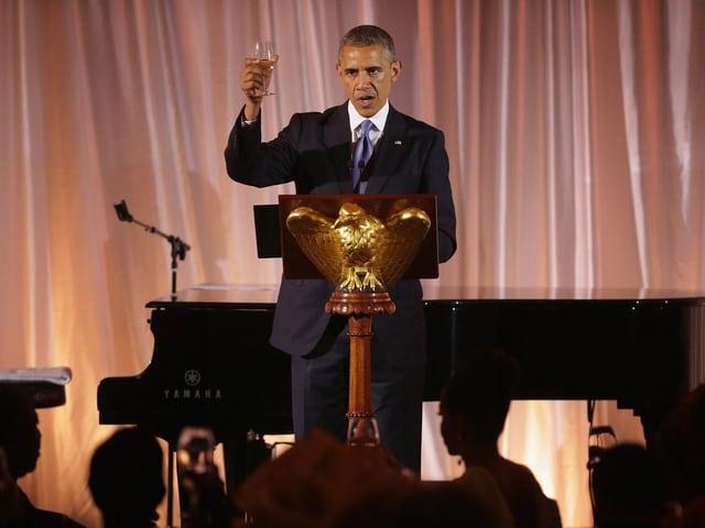 Obama am Rednerpult, er hebt ein Glas zum Toast.