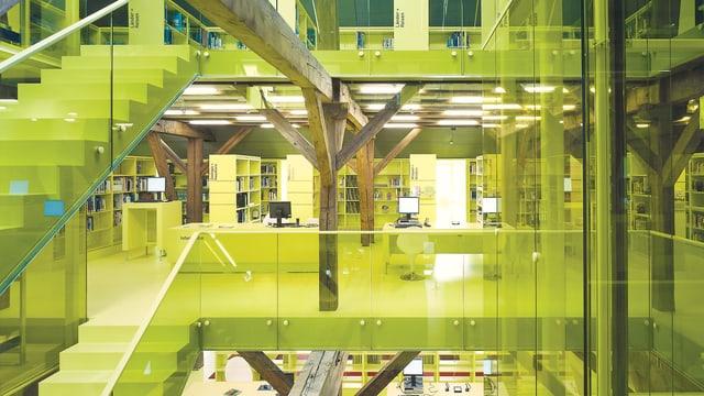 Mehrstöckiges Gebäude von innen. Ausser alten Holzbalken sind fast alle Bauelemente in leuchtenden gelbgrüne Farbtönen.