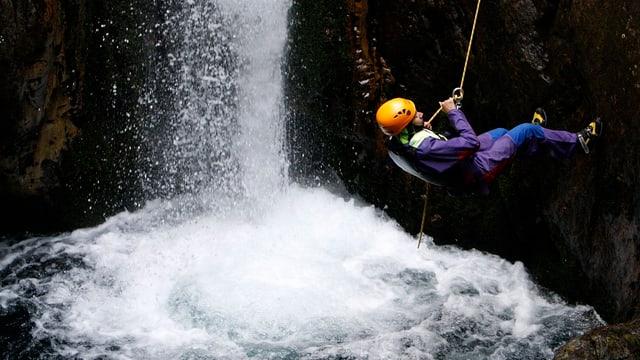 Ein Mann seilt sich von einem Felsen in einen Bach ab, hinten ein Wasserfall.