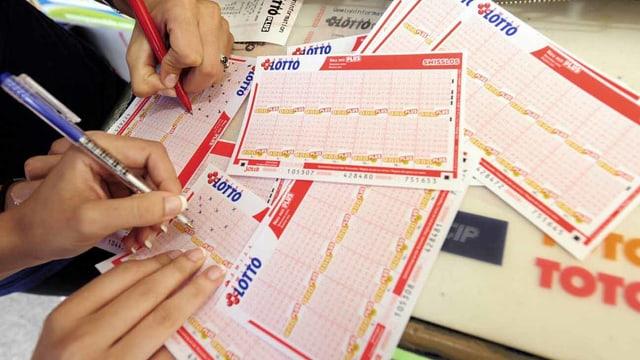 Menschen füllen Lottoscheine aus.