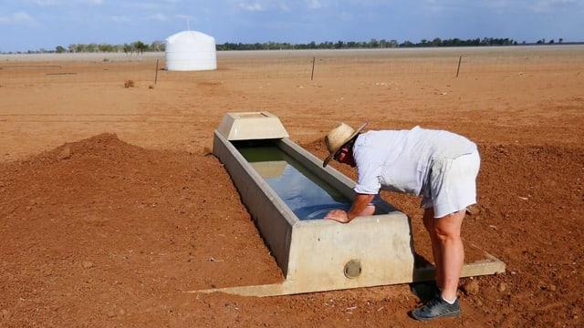 Eine Frau prüft das Becken eines Brunnens.