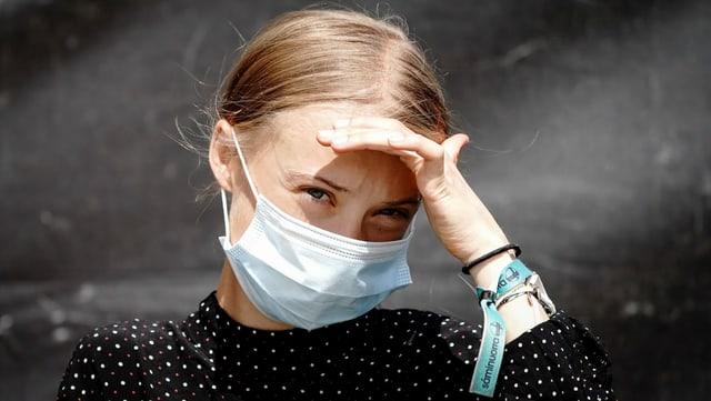 Greta Thunberg trägt eine Hygienemaske und blickt ernst in die Kamera, eine Hand an der Stirn, um die Augen von der Sonne abzuschirmen.