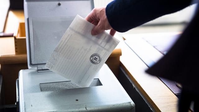 Mann wirf Wahlzettel in eine Urne.