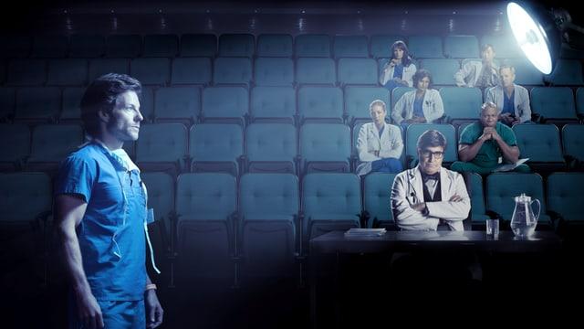 Ein Arzt steht im Scheinwerferlicht. Wie bei einem Sportspiel schauen ihn seine Kolleginnen und Kollegen von der Tribune aus an.