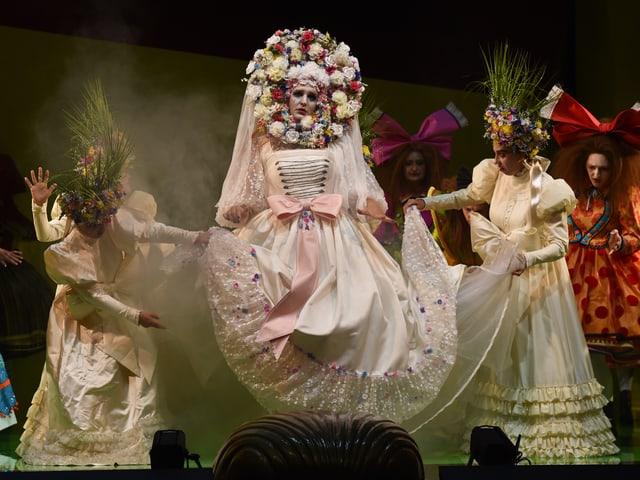 Eine Frau in einem weissen Kleid mit Blumenkranz um den Kopf