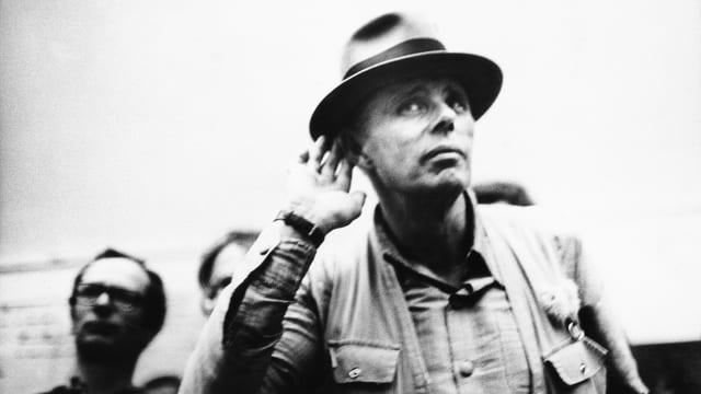 Ein Mann mit Hut hält seine Hand an ein Ohr und lauscht