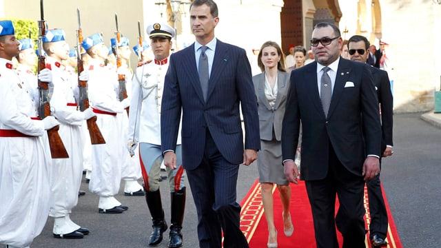 Felipe und Mohammed schreiten auf einem roten Teppich eine marokkanische Garde ab, hinter ihnen Letizia.