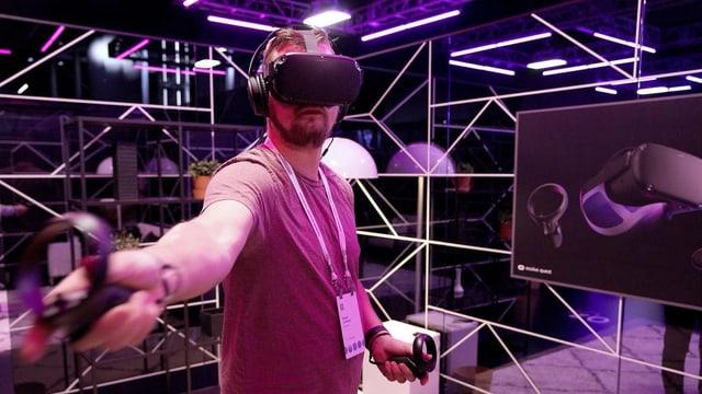 Ein Mann mit einer Virtual-Reality-Brille auf dem Kopf und Controllern in den händen steht in einem violett beleuchteten Raum.