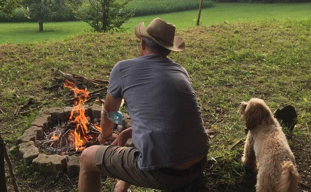 Mann sitzt mit Hund am Feuer