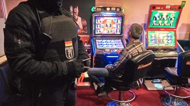 Mann sitzt vor Spielautomat. Daneben steht ein Polizist in Schutzkleidung.