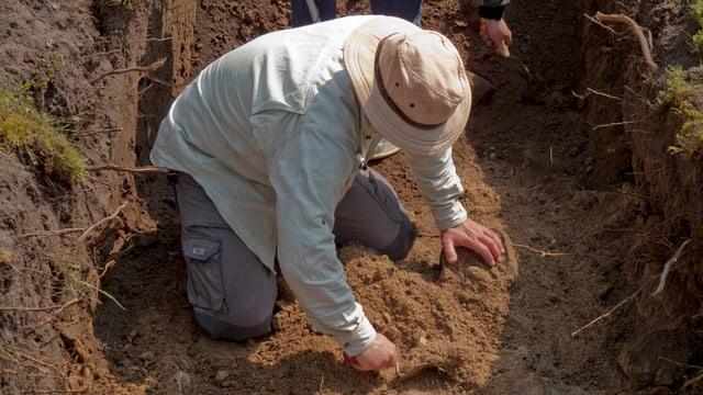 Ein Mann mit Panamahut gräbt in der Erde.