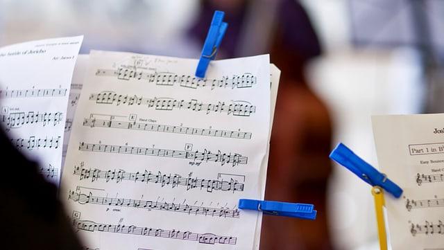 Kopierte Notenblätter, deren Herunterfallen vom Notenständer durch Wäscheklammern verhindern werden soll.