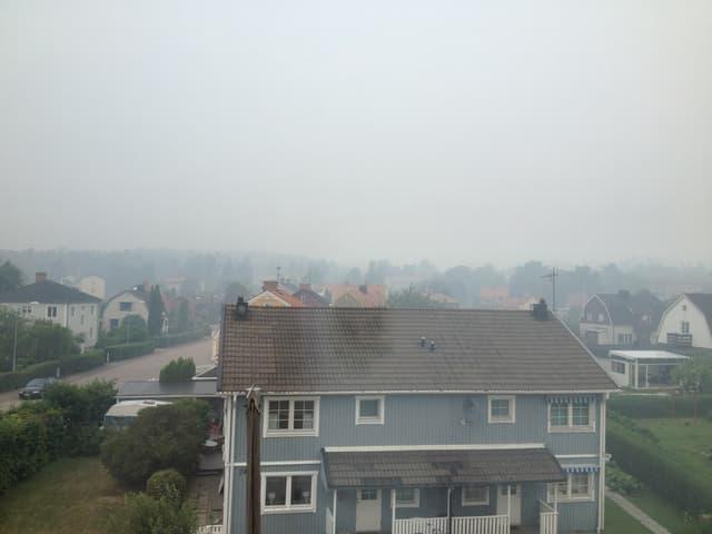 Blick auf Häuser, über denen eine Rauchwolke hängt.