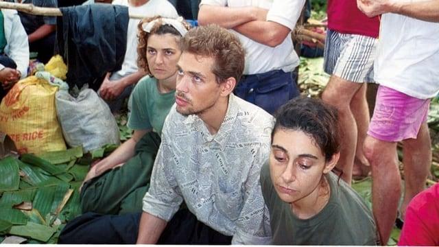 Zwei junge Frauen und ein junger Mann sitzen auf dem Boden, um sie herum andere Menschen.