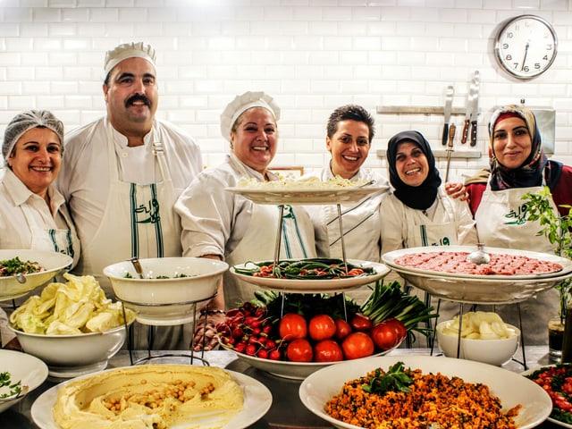 Eine Gruppe von Frauen in Kochuniform stehen hinter einem Tisch mit verschiedenen Speisen.