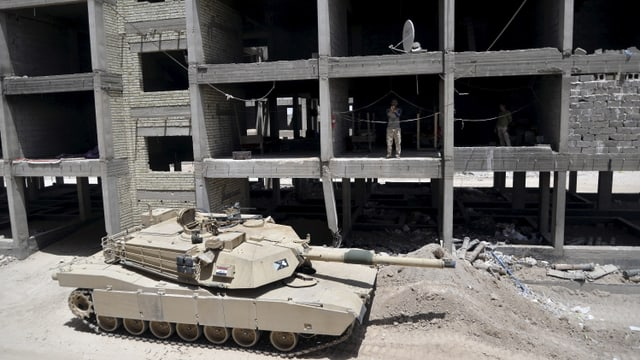 Ein Panzer vor einer Häuserruine.