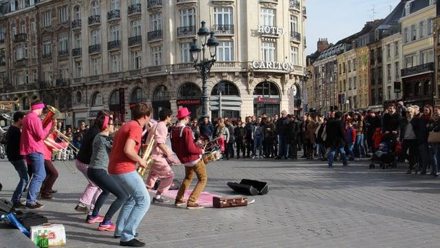 Students che fan musica sin las plazzas da Lille.