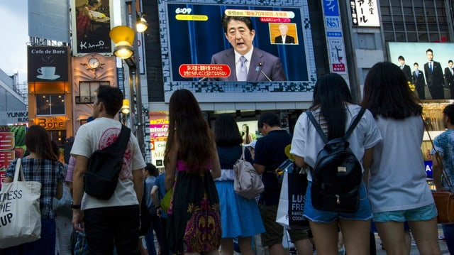 Menschen stehen in einer städtischen Fussgängerzone vor einem grossen Bildschirm, auf dem Premier Abe spricht.