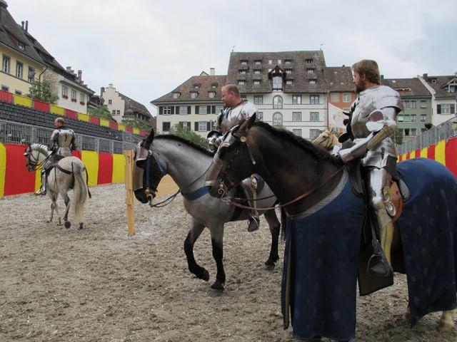 Männer zu Pferde und in Rüstungen besichtigen den Turnierplatz Herrenacker.