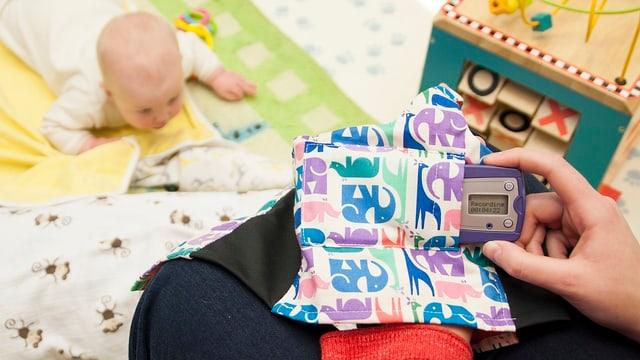 Ein Baby liegt auf dem Boden, davor hält die Mutter ein kleines Gerät in der Hand.