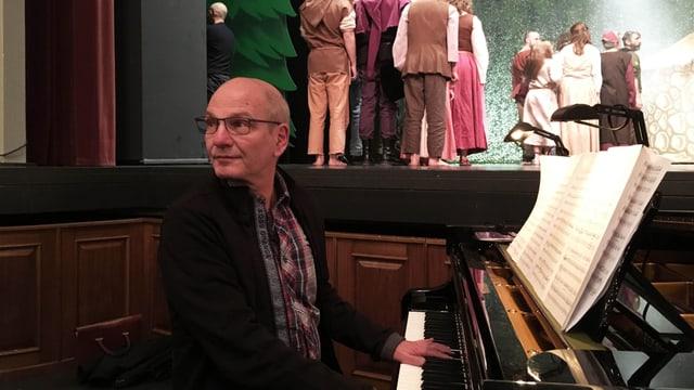 Ein Mann sitzt am Klavier und spielt, im Hintergrund stehen Kinder auf einer Theaterbühne.