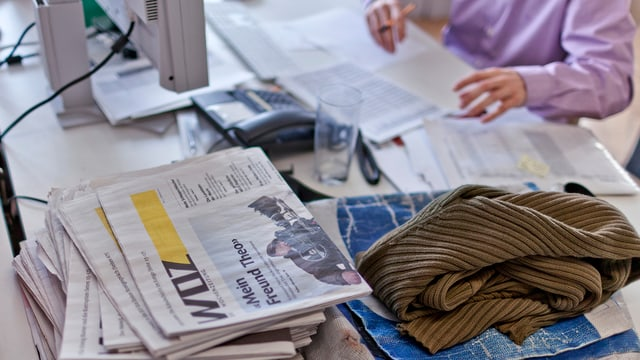 Eine WOZ-Mitarbeitende sitzt am Schreibtisch über einem ausgedruckten Blatt vor einem PC, daneben ein Stapel diverser Ausgaben der WOZ.
