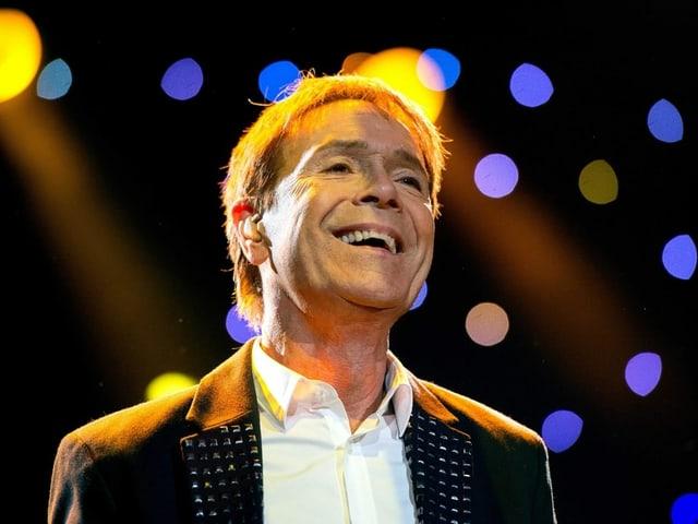 Cliff Richard um die 70 Jahre alt steht mit strahlendem Gesicht im Scheinwerferlicht.