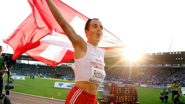 Viktor Röthlin hält die Schweizer Fahne in die Höhe.