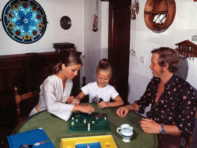 Die junge Familie spielt Halma im rustikal eingerichteten Wohnzimmer.