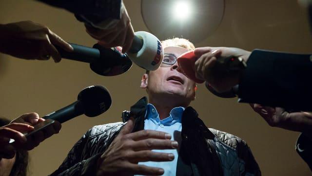 Roger Köppel von unten, mehrere Mikrofone vor seinem Gesicht, an der Decke ein Spotlicht.
