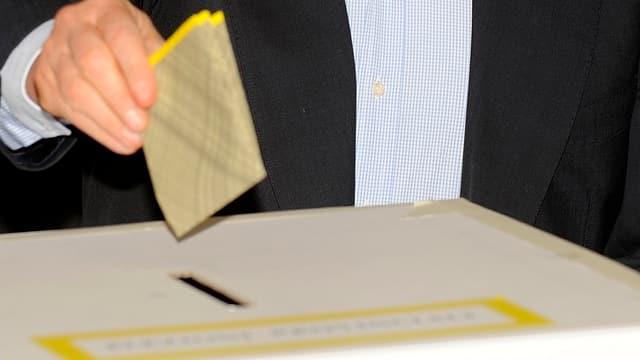 In maun che metta in cedel da votaziun en in'urna.