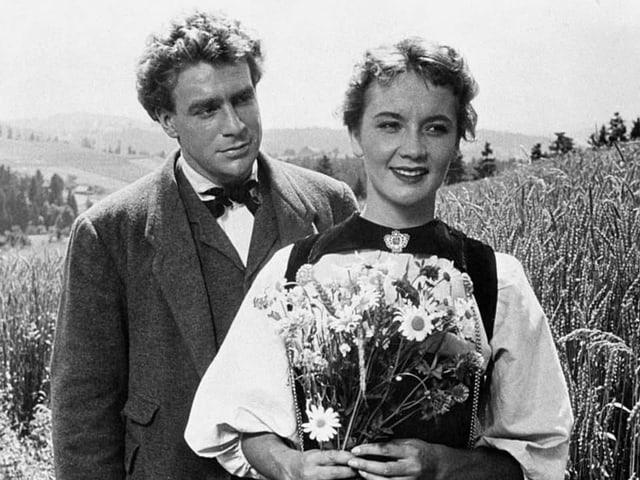Schwarz-Weiss-Aufnahme: Liselotte Pulver in Bernertracht und mit Blumenstrauss. Dahinter steht Hannes Schmidhauser.